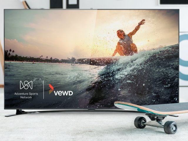 Image of surfer inset in a TV that is surrounded by a skateboard and a bicycle